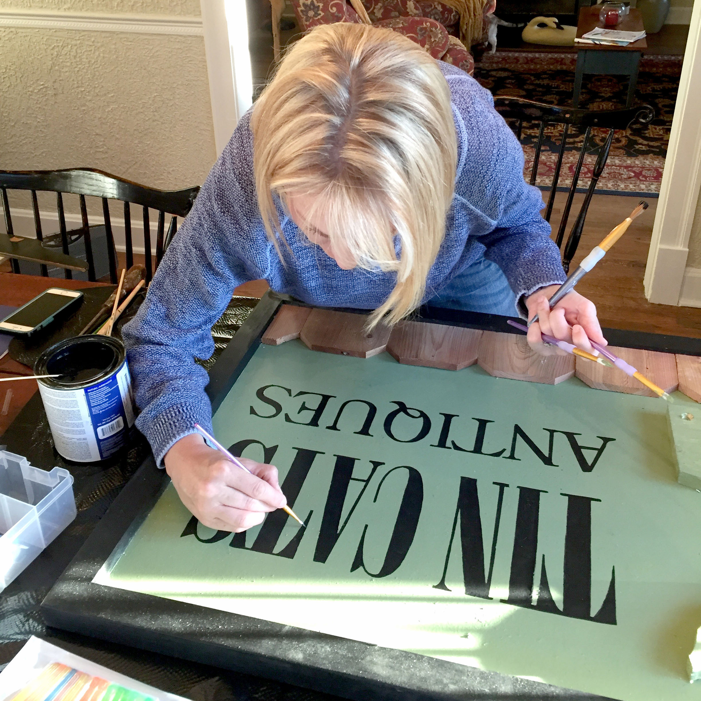Jami Wilmarth touches up the lettering on the Tin Cats Antiques sign.